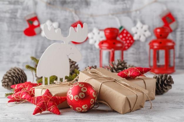 Горящий фонарь и рождественские украшения на белом столе