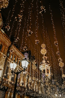 お祝いのクリスマスデコレーションで夜の街の燃えるランタンと金色のライト