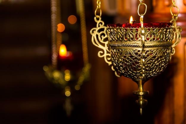 天使をイメージした古い銅製の教会のランプで燃える光