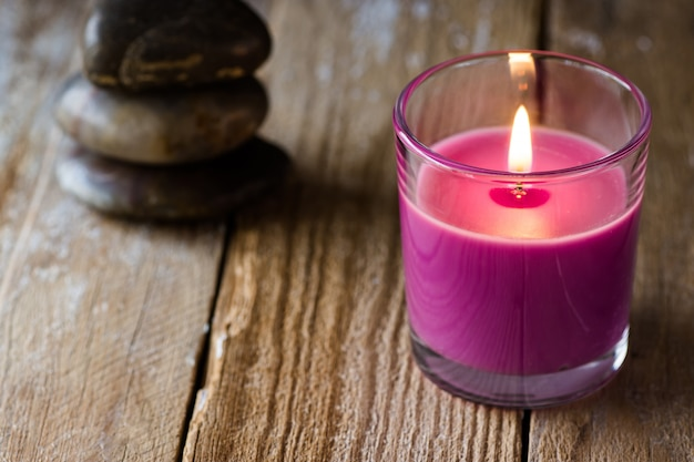 Burning lilac lavender candle stack of balanced zen stones on wood background
