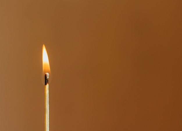 Burning match on blurry brown