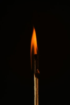Burning match close-up on a black. red flame. ignition matchstick isolated on black. copy space.