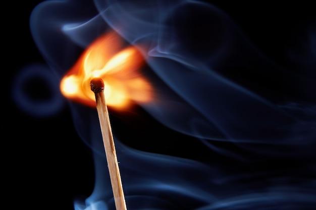 Burning match with smoke on black background