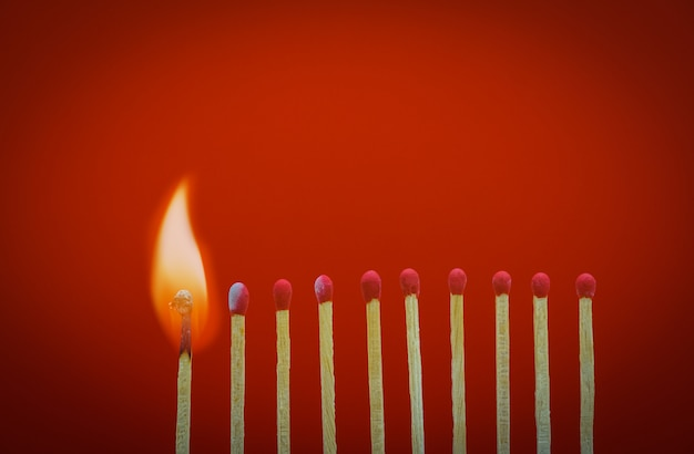 Burning matchsticks setting fire to its neighbors