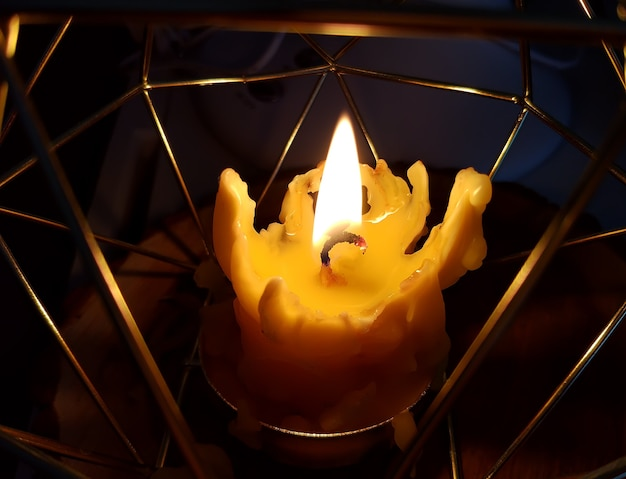 Burning melting wax candle in modern style metal candlestick