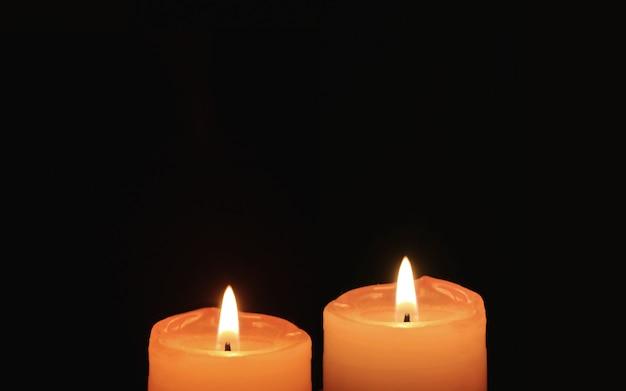 Burning pair of orange candles on black background