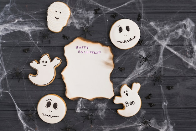 Burning paper in cobweb around gingerbread and spiders