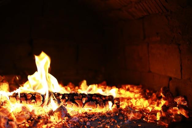 불타는 붉은 뜨거운 불꽃은 큰 불에서 날아갑니다. 화재의 주제에 아름 다운 추상적인 배경입니다. 불타는 석탄, 검은 배경에 날아가는 불타는 입자.