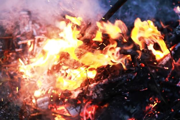불타는 붉은 뜨거운 불꽃은 큰 불에서 날아갑니다. 불타는 석탄, 검은 배경에 날아가는 불타는 입자.