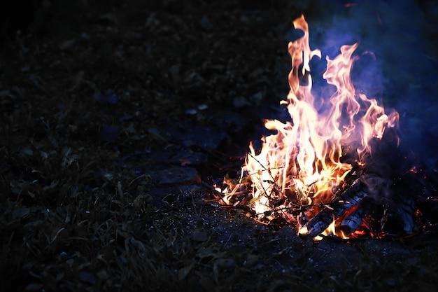 불타는 붉은 뜨거운 불꽃이 큰 불에서 날아갑니다. 불타는 석탄이 날아가는 불타는 입자