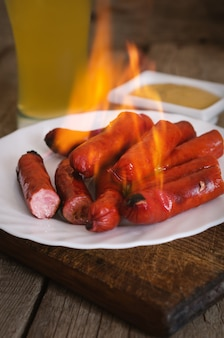 Burning sausages on plate with mustard sauce