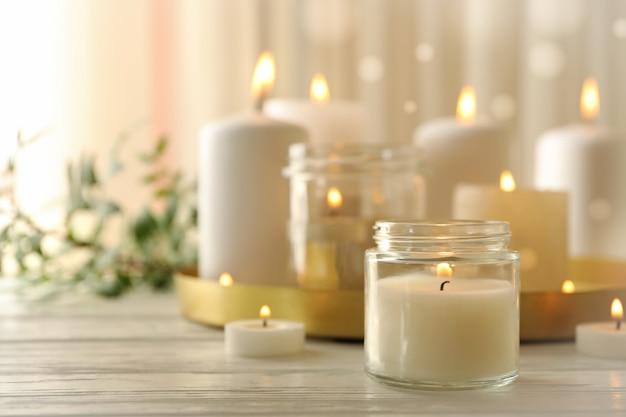 白い木製のテーブルでリラックスするための香りのキャンドルを燃やす