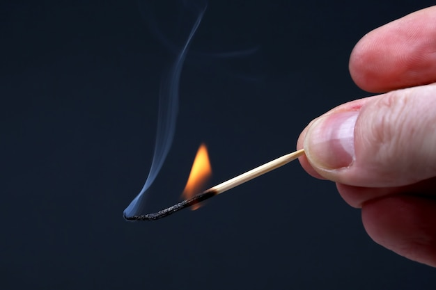 Burning and smoking wooden match in hand on dark