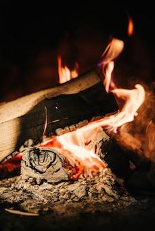 自宅の石造りの暖炉でくすぶっている火を燃やす