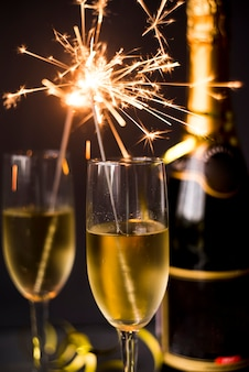 Burning sparkler in champagne glass on dark background