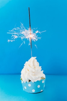 Burning sparkler on creamy cupcake against blue backdrop