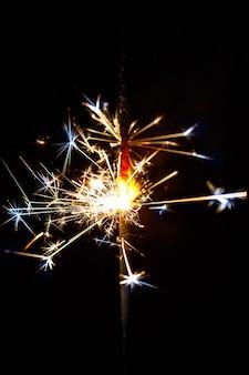 黒の背景のぼかしで分離された燃える線香花火