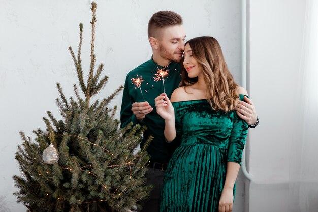 パーティー客の手で燃える花火。カップルの人々は美しく飾られたクリスマスツリー、クリスマスコンセプトの近くで幸せにクリスマスと休日を祝っています