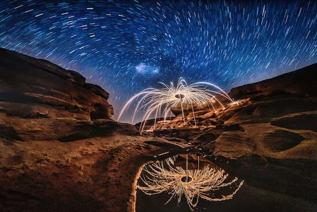 Burning steel wool on the rock with milky way near the river at sam phan bok in ubonratchathani unseen in thailand. the grand canyon of thailand.
