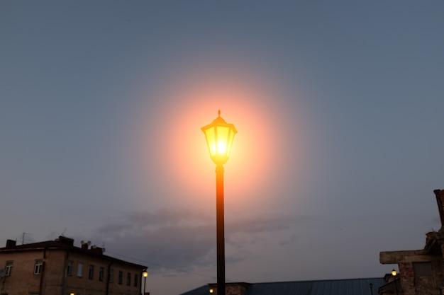 空に対して街灯を燃やす。夕方の街