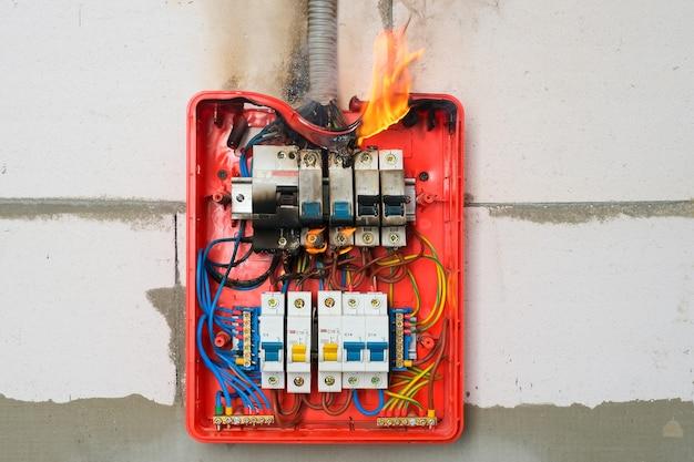 壁のクローズアップでの過負荷または短絡による配電盤の燃焼