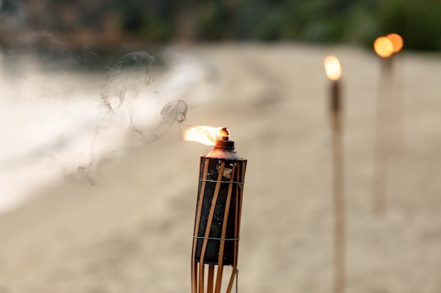 Burning torches stand in row on sand beach