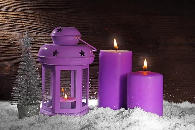 木製の背景に雪と紫のキャンドルを燃やす