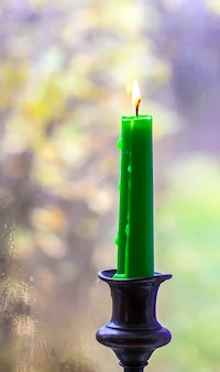 Burning wax candle in brass candlestick in country house interior.
