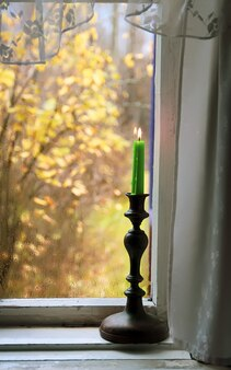 Burning wax candle in brass candlestick on the wooden window sill of in country house interior.