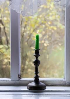 시골집 내부의 나무 창틀에 있는 황동 촛대에 왁스 초를 태우고 있습니다.