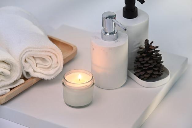 흰색 테이블에 왁스 캔들, 수건, 샴푸 병을 태우세요.