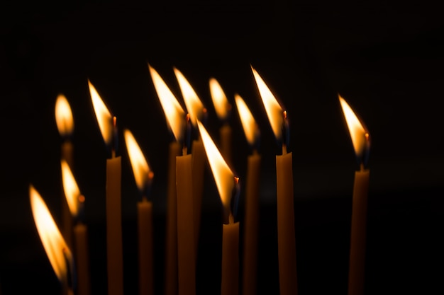 Burning wax candles against the window in a dark room