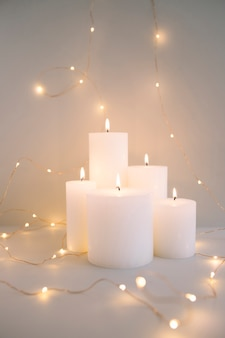 Burning white candles surrounded with illuminated fairy lights on grey background
