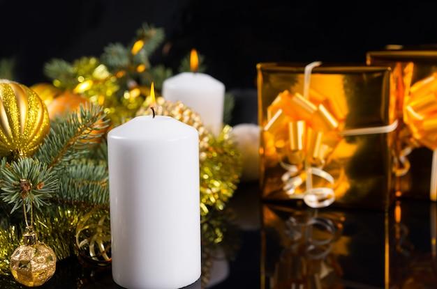 松の枝と金色の装飾をアレンジした白いクリスマスまたはアドベントキャンドルを、コピースペース付きの黒の上に豪華なゴールドギフトと一緒に燃やします