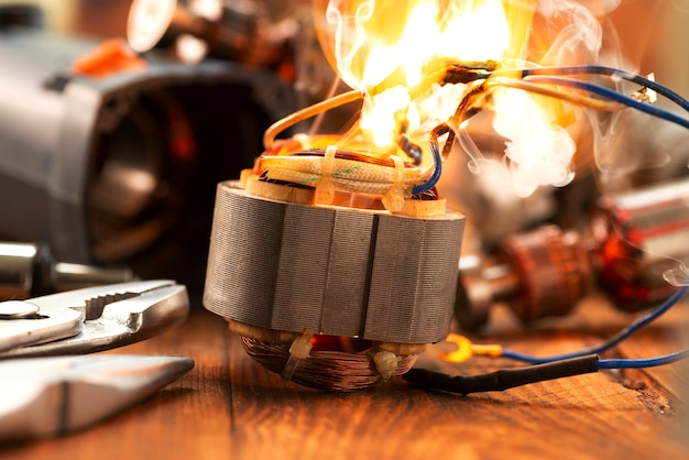Burning wires on the details of an electrical appliance on a wooden table in a repair shop. power tool repair.