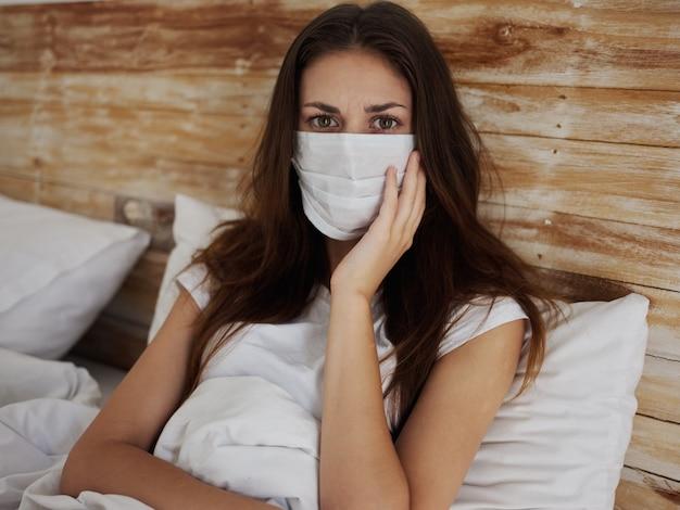 의료용 마스크를 쓴 불타는 여성은 침대에 누워 손 검역 감염으로 얼굴을 만진다