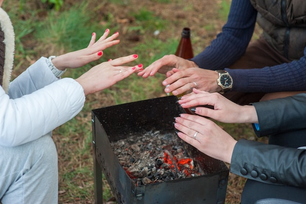 Burning wood in the grill and red coals with stream coming up from it. little boy in red coat is warming his frozen hands above the flames of the grill brazier. picnic in winter