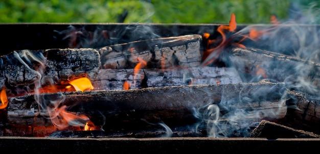 バーベキューグリルで薪を燃やす。直火、炎、自然の中で燃えている薪からの煙
