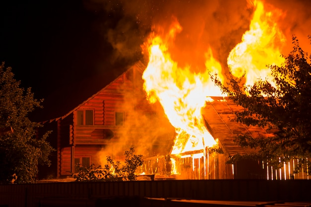 Burning wooden house at night