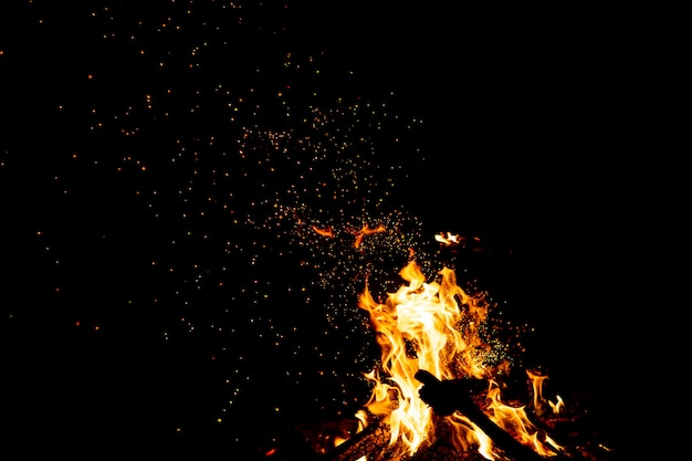 Burning woods with fire sparks, flame and smoke at night.