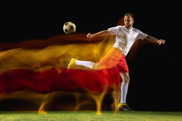 Burning. young caucasian male football or soccer player in sportwear and boots kicking ball for the goal in mixed light on dark wall. concept of healthy lifestyle, professional sport, hobby.