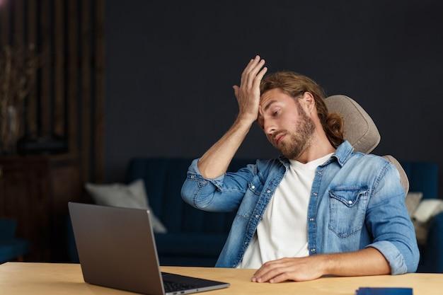 번아웃 및 과로 개념입니다. 노트북으로 사무실에서 초과 근무를 하는 피곤한 사업가. 긴 머리를 가진 잘생긴 곱슬머리 청년이 금융 위기를 극복하기 위해 아이디어를 찾고 있다고 강조했습니다.