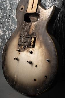 어두운 벽의 배경에 불된 깨진 된 오래 된 일렉트릭 기타.