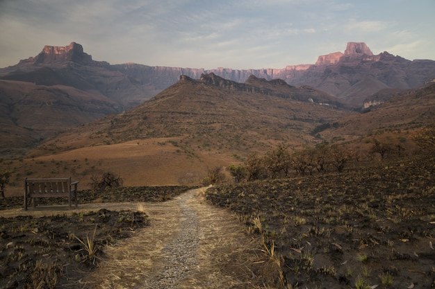 Burnt dry grass field in the desert with a narrow pathway and beautiful rocky mountains