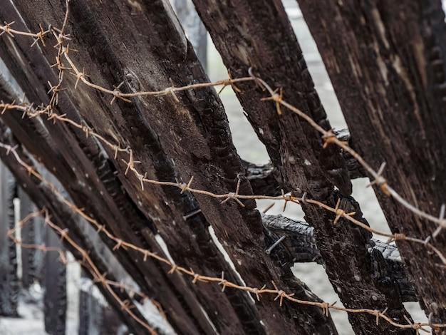 有刺鉄線で焦げた柵。注意深く思慮のない火の取り扱いの結果。