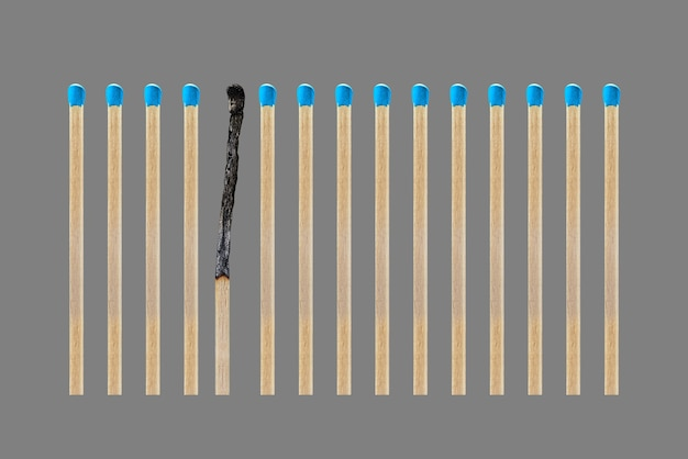 A burnt match in a row of whole matches isolated on a gray background