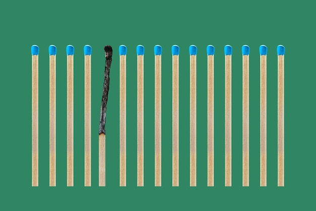 A burnt match in a row of whole matches isolated on a green background