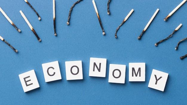 Burnt matches arrangement with economy word