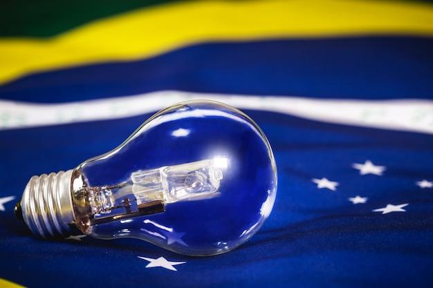 ブラジルの国旗のテクスチャ、ブラジルのエネルギー危機の概念の上に電球を燃やしました