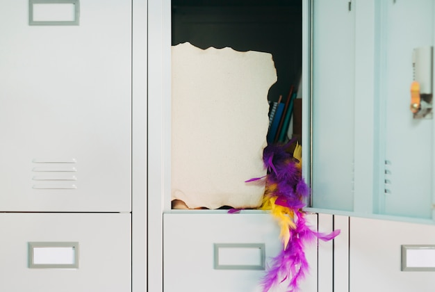 Burnt page with yellow and purple feather boa hanging from open safety locker